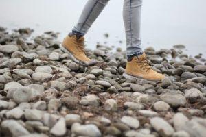 Mujer caminando entre las piedras con zapatillas impermeables